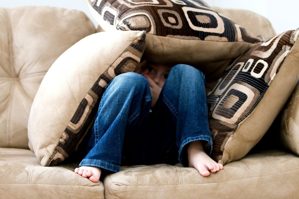 A boy in blue jeans hiding under pillows on a couch
