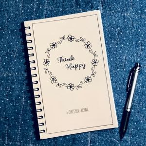 "A blush-colored journal with the words ""Think Happy"" on a denim blue background"