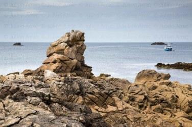Chalutier au mouillage devant l'ile de Sein, sur la cote nord. Un goeland au pied du rocher.