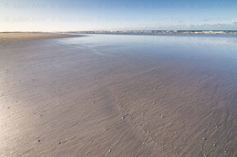 Plage et reflets sur le sable dans la baie d'Audierne.