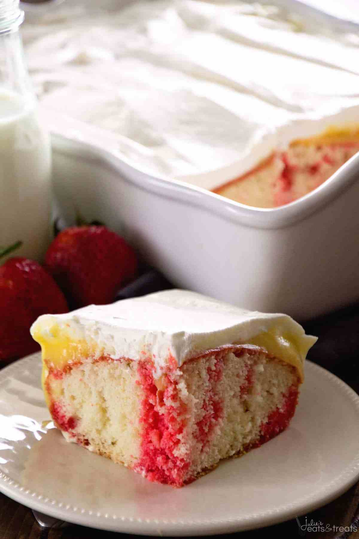Strawberry Poke Cake dished up on a white plate with strawberries and cake in the background.