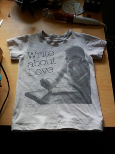 """Cut-down pink Belle and Sebastian T-shirt, picture of girl writing with """"Write About Love"""" caption."""