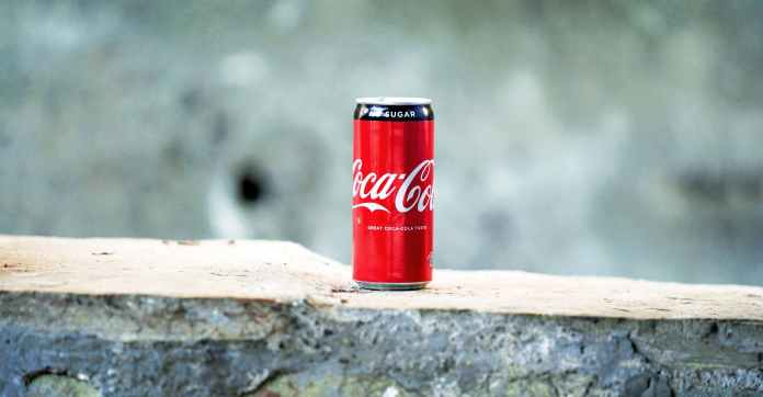 coca cola can on brown concrete surface