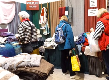 customers rummaging thro the woven throws made by Curlew Weavers - who have a mill in Dyfed - to visit phone 01239 851357