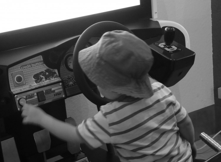 Hier ist ein kleines Kind bei der Bedienung eines Rennfahrer-Spielautomaten-Dings zu sehen. (Entschuldigung. Ich weiß nicht, wie so ein Gerät richtig heißt)