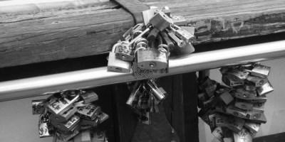 Hier sieht man ein Bild verschiedener kleiner Schlösser, die an einer Brücke befestigt sind.