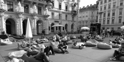 Hier sieht man Menschen auf dem Hauptplatz in Graz. Sie sitzen in Sitzsäcken und Sonnenstühlen, Z.T unter Schirmen, ruhen und lesen.