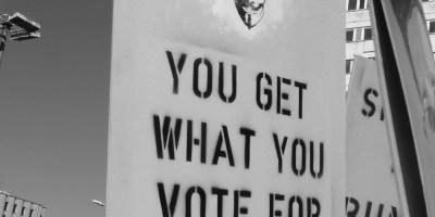 """Hier ist ein Plakat mit einem Aufdruck einer Anonymous-Maske zu sehen. Der Spruch, der ergänzend darunter steht, lautet """"You get what you vote for"""". Das Schild habe ich auf der """"Freiheit statt Angst 2013"""" in Berlin aufgenommen."""