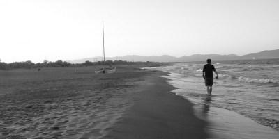 Hier ist ein einsamer Wanderer an einem spanischen Strand zu sehen. Eine Reise, in diesem Fall zu Fuß