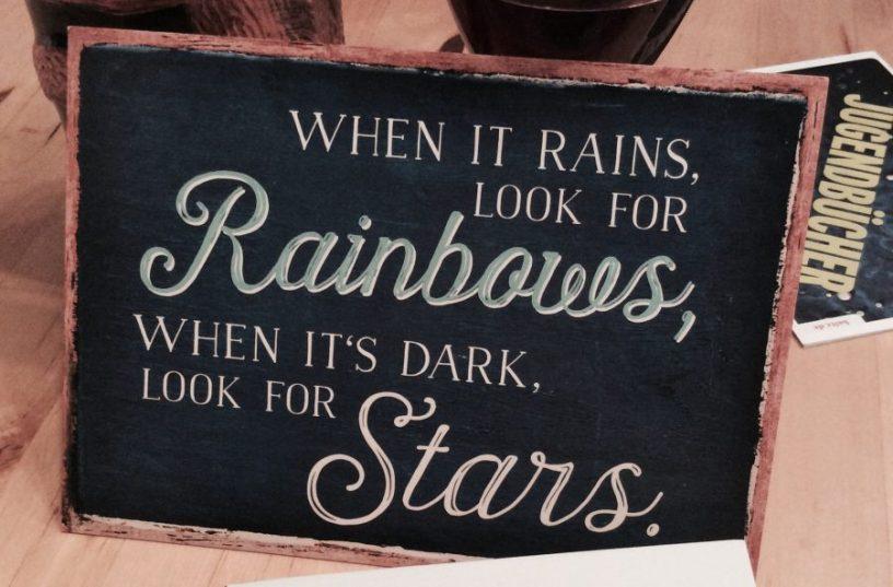 """Hier ist ein Bild von einer Postkarte zu sehen, auf der die englische Aufschrift: """"When it rains, look for rainbows, when its dark, look for stars"""" steht"""