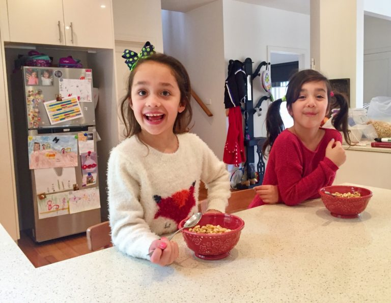 Seven year old twins, Antonia (left) and Iliana (right) eating cereal at home. Their mother, Vivian Papadima, is concerned about what goes into their food. Picture: Sofia Vamvakidou