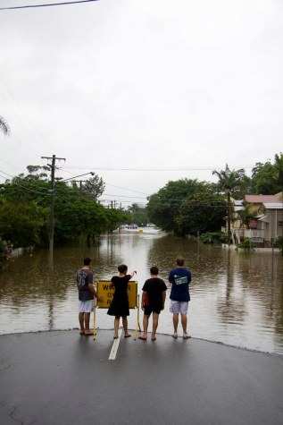 Four young men stand at the end of a flooded street
