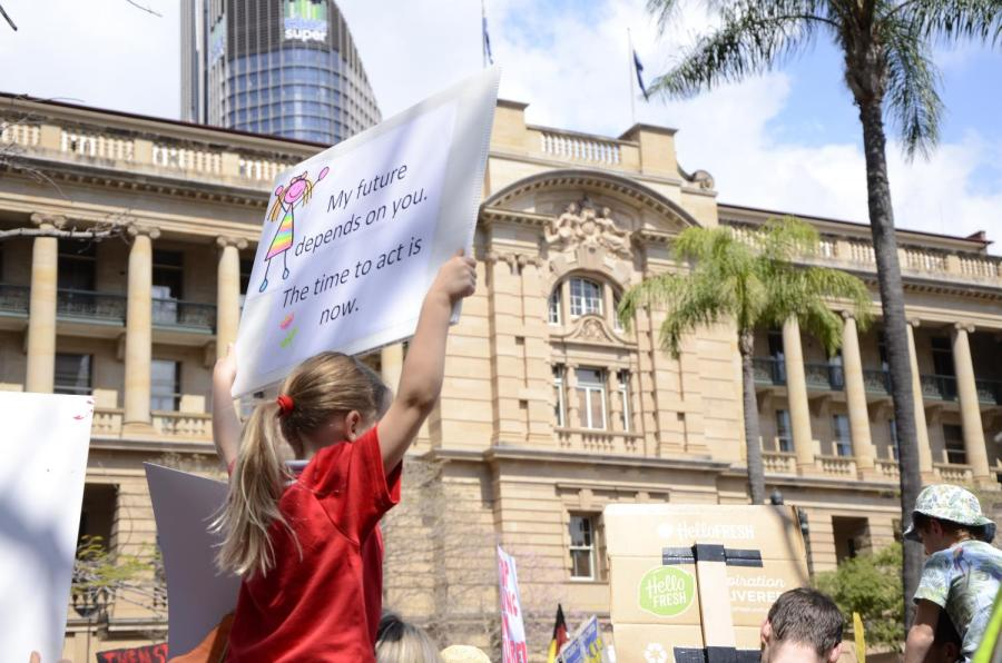 Child holds a placard aloft reading: My future depends on you. The time to act is now.