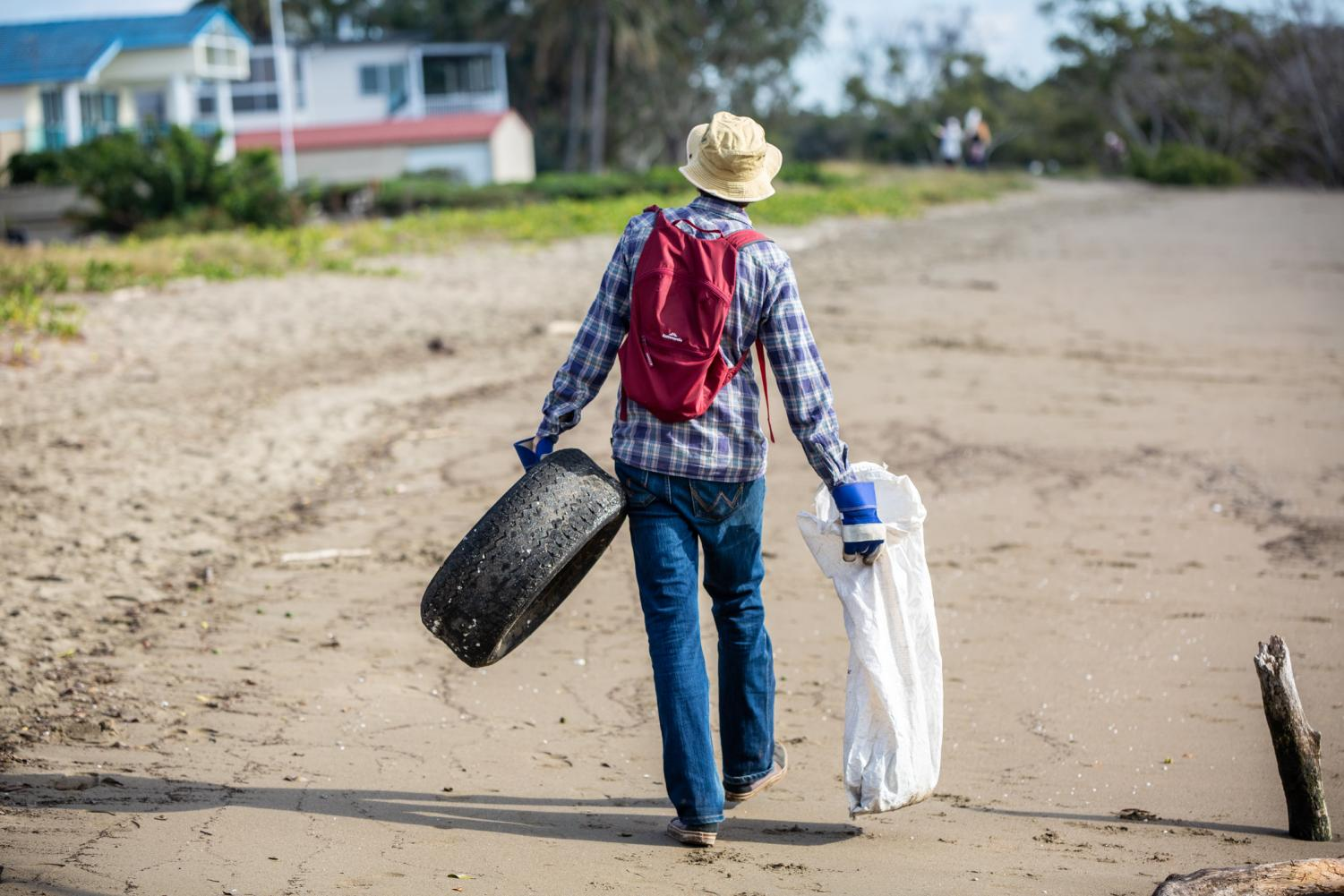 Volunteer returns carrying a discarded rubber tyre and bag of plastic debris after scouring the beach in search for debris that was dumped or washed ashore.