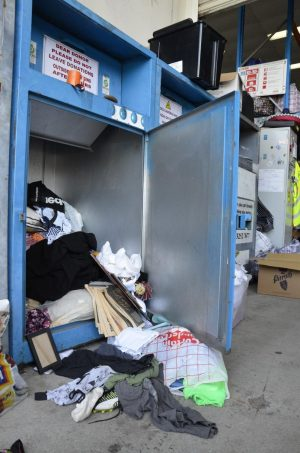 Open charity bin with contents spewing outside, a good portion of them unable to be recycled