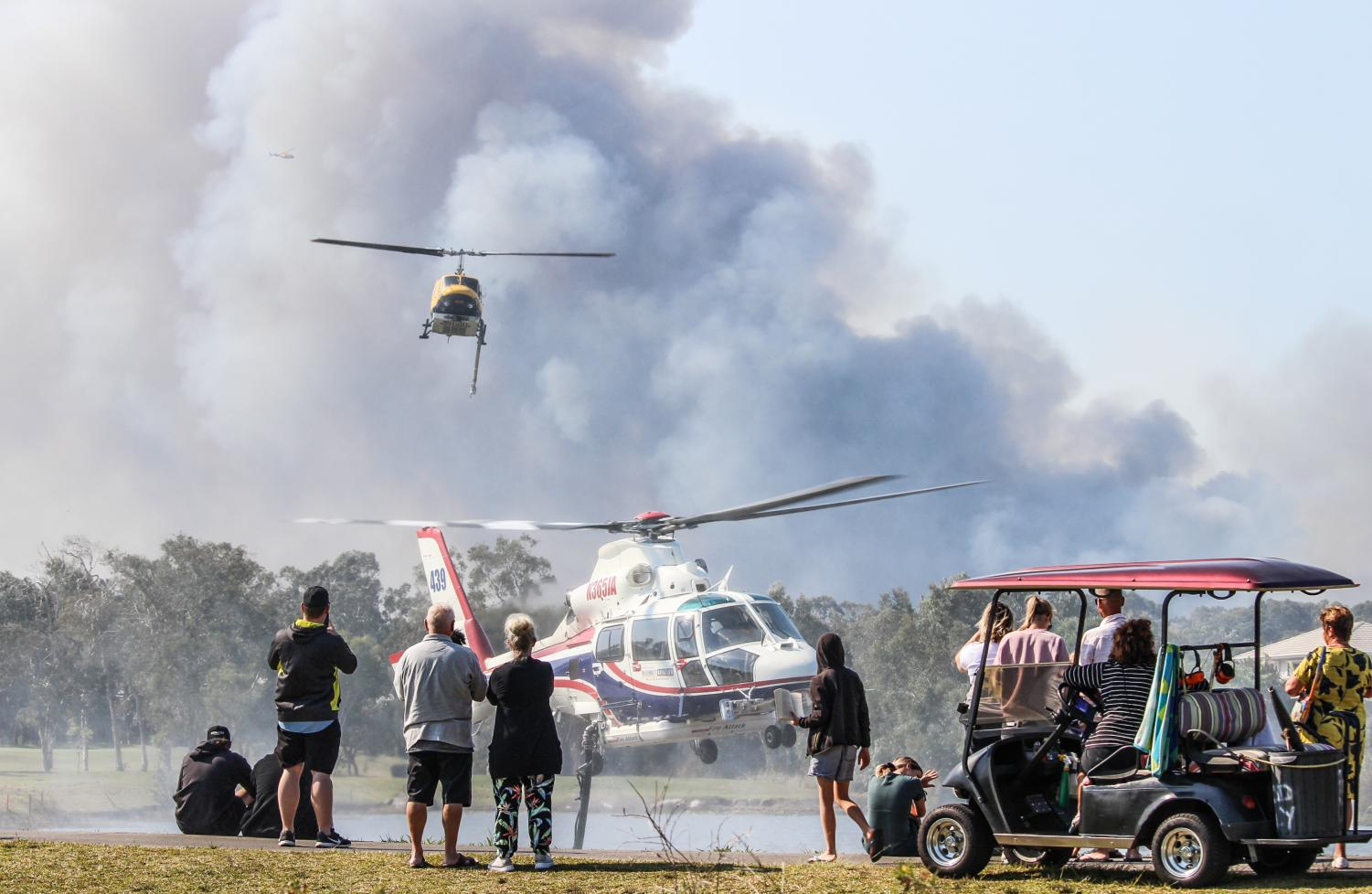 Two water-bombing helicopters swoop in to refill at the Peregian Springs Golf Club before flying back to fight the bushfire that threatened the area on September 10.