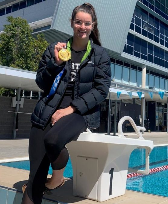 woman by a pool with a gold medal