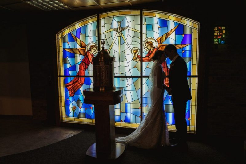 Catholic wedding couple in front of stained glass in Roseville, MI.