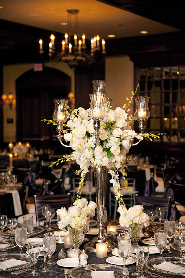 chair covers and more houston replacement webbing for lawn chairs beautiful reception table setting large silver candelabra with ivory candles white green floral arrangement as centerpiece dishes dark purple tablecloth photo by