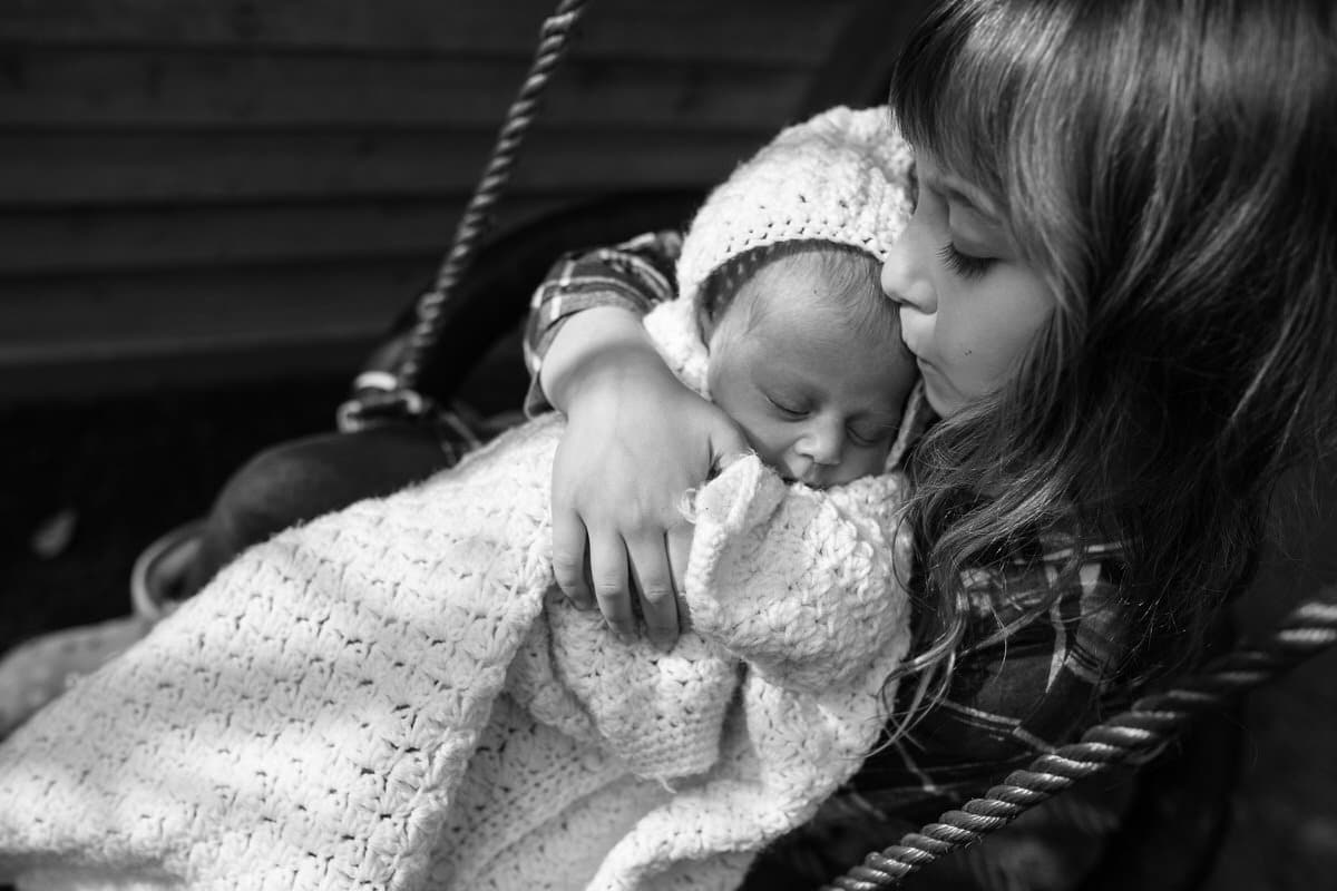 Girl holding baby sibling.