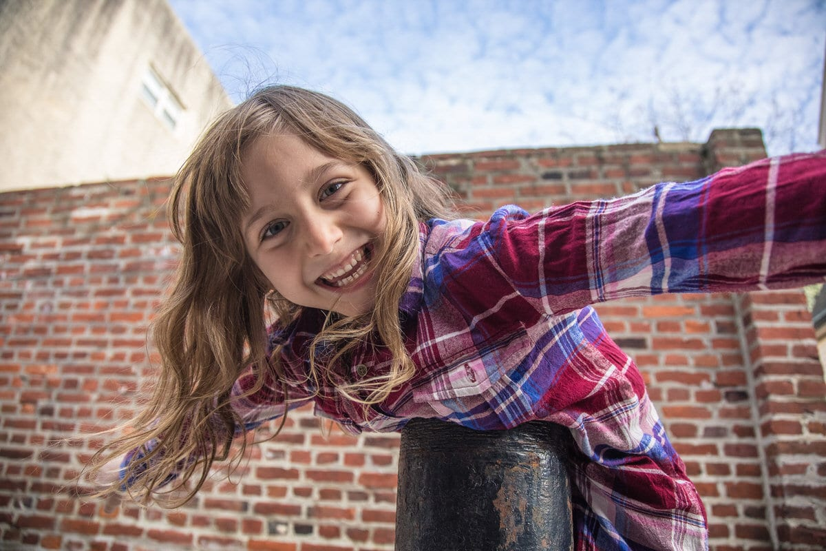 Girl playing outside by Philadelphia brick wall.