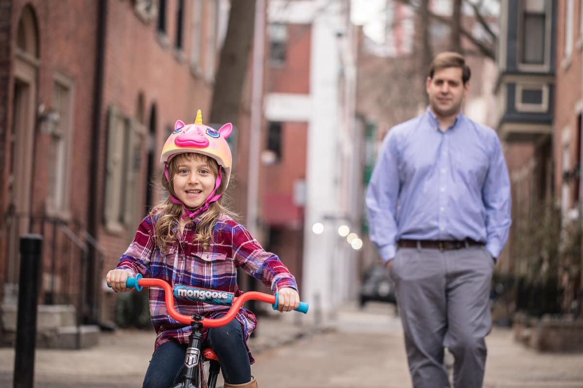 Father helping daughter ride a bike in Old City Philadelphia.
