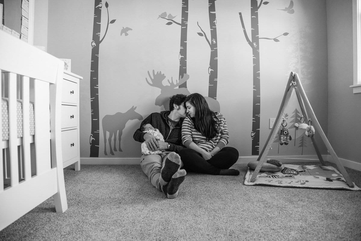 Mother and father sit on floor of baby's nursery.
