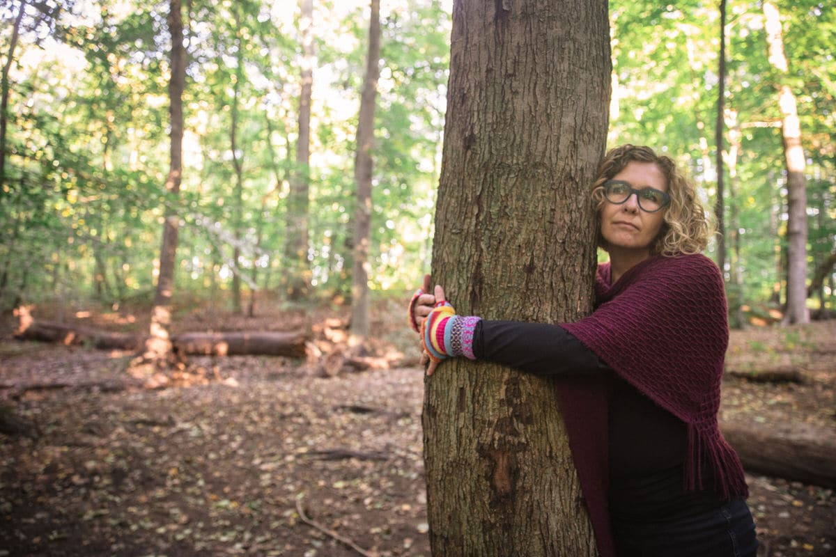 Woman hugs tree in forest.