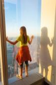 Meine große Tochter lehnt sich gegen eines der großen Fenster des One World Trade Center.