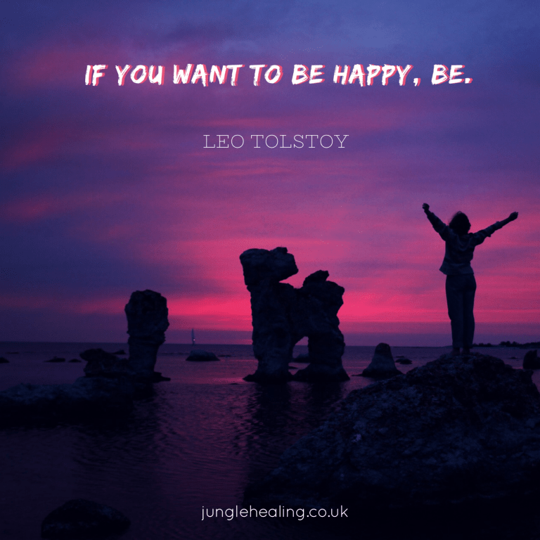 Affirmation of the week. Quote of: 'If you want to be happy, be' by Leo Tolstoy set against a background of a pink and purple sunset with a woman holding her arms out to the sky.