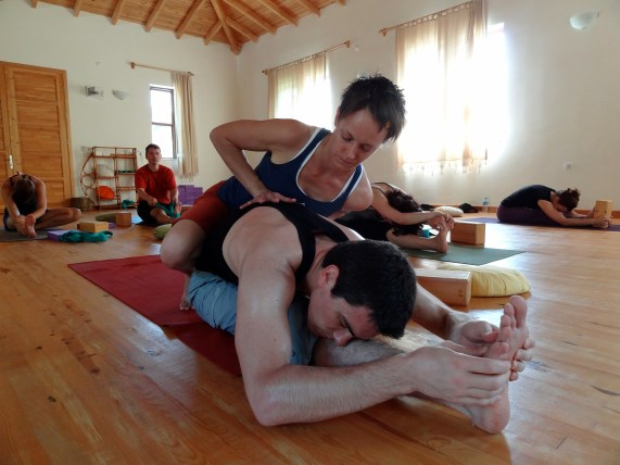 Assisting janu sirsasana. Photo by Handan Karadag