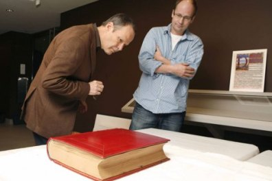 "Rubin Museum of Art chief curator, Martin Brauen, left, and Felix Walder, great-grandson to Carl Jung, inspect Carl Jung's ""The Red Book"" (Photo: Rubin Museum)"