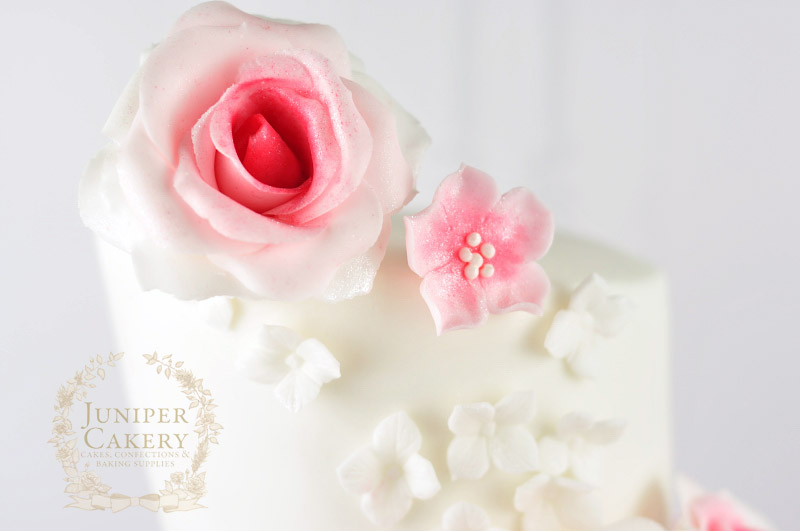 Pink rose and cherry blossom with hydrangeas on a topsy turvy cake by Juniper Cakery