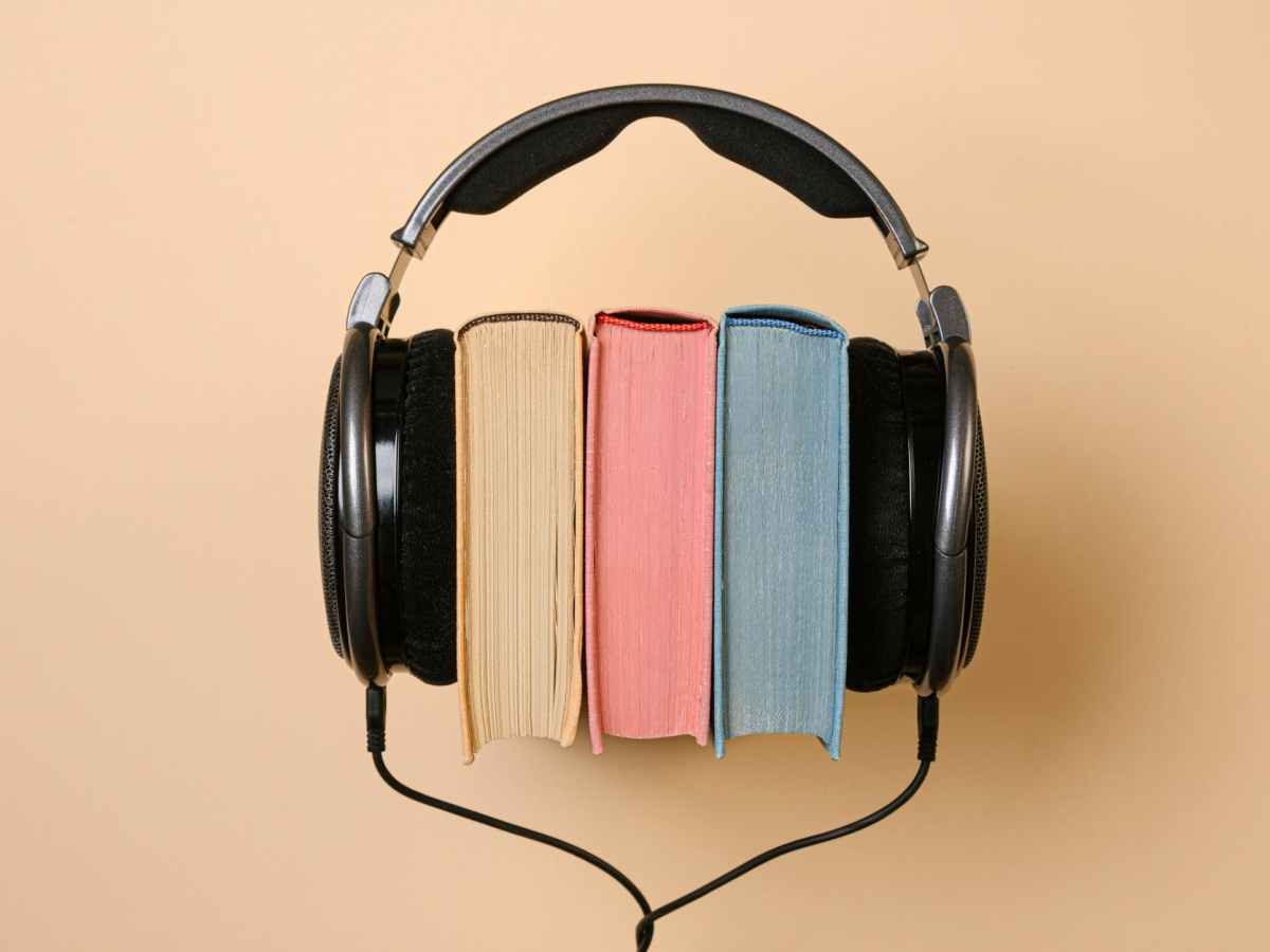 black corded headphones with colorful books in between