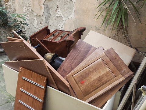 Old furniture and rubbish piled up in a garden