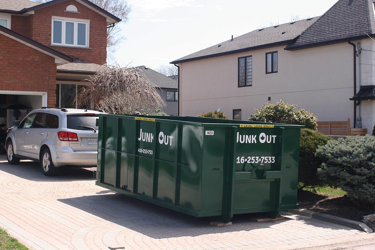 Bin rental toronto - green Junk Out dumpster bin in a residential driveway on a sunny day.