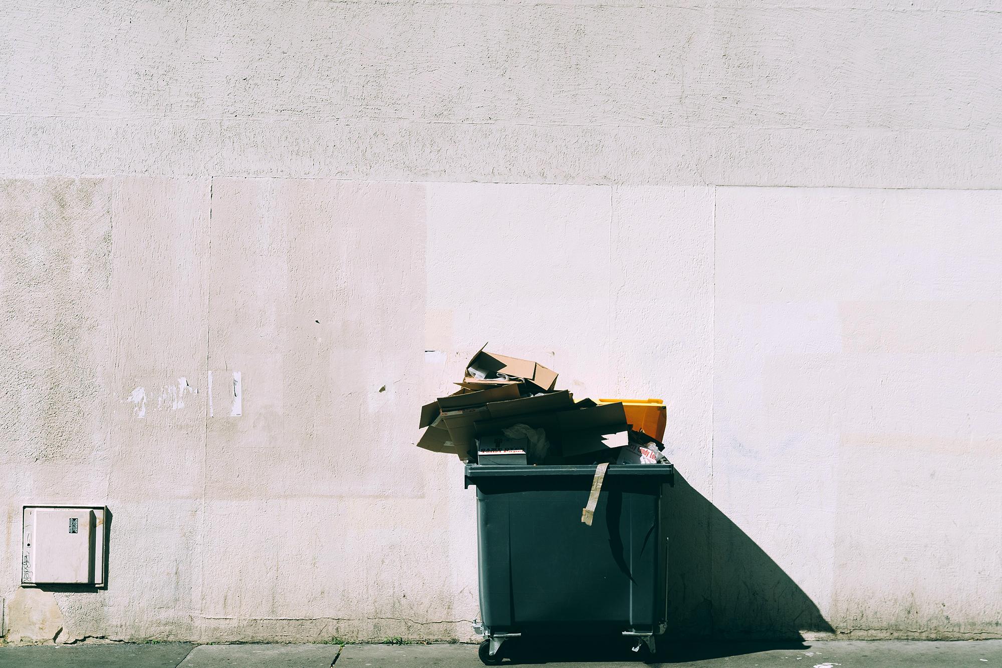 Dumpster bin full of cardboard boxes