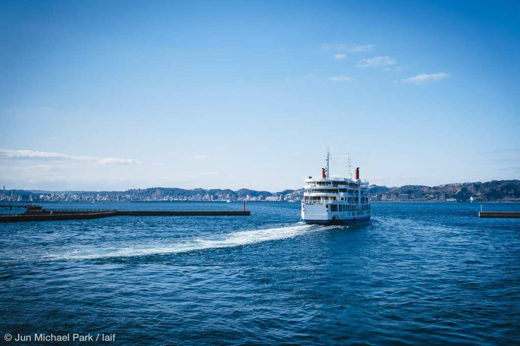 KAGOSHIMA, JAPAN - February 3, 2016: A ferry leaves from the Sakurajima Pier to Kagoshima City. Sakurajima stands for Cheery Blossom Island in Japanese and is known for its active volcano. The lava from the 1914 eruption connected the former island to the Osumi Peninsula. The regular ferry service connecting Sakurajima and Kagoshima City was implemented on November 19, 1934.