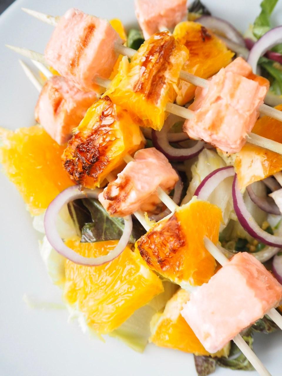 Fertige Orangen-Lachsspieße Nahaufnahme auf dem Teller mit Salat