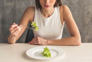 slender young woman eating lettuce 45