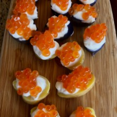 Potatoes topped with crème fraîche and salmon roe