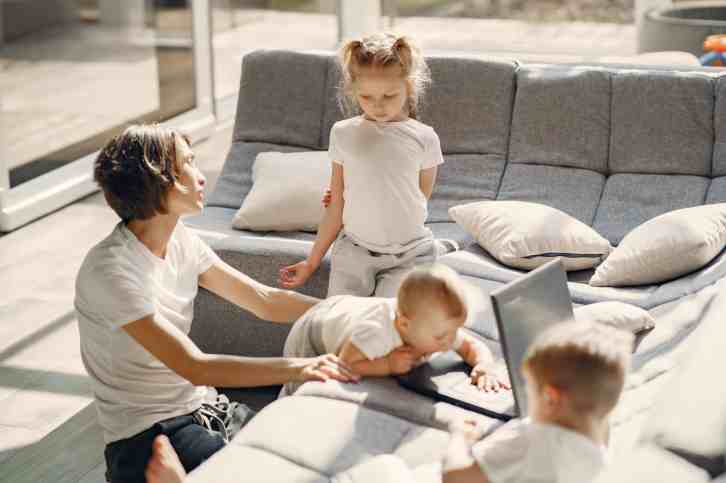 Image of a mother kneeling on the floor next to the couch while a baby crawls from her lap onto the couch, a toddler sits on the couch looking at them, and a preschool girl stands next to her and looks also.