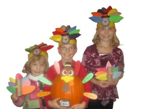 Picture of 3 children wearing turkey headbands and holding Thanksgiving crafts