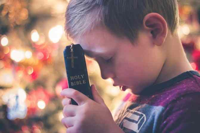 Image of boy holding Bible up to his forehead with his eyes closed in prayer and Christmas lights in background to show establishing an Advent calendar devotional tradition in the family.