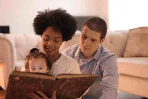 Image of African-American woman holding a young girl on her lap and reading from a book with a brown cover while a white man looks over her shoulder at the book.