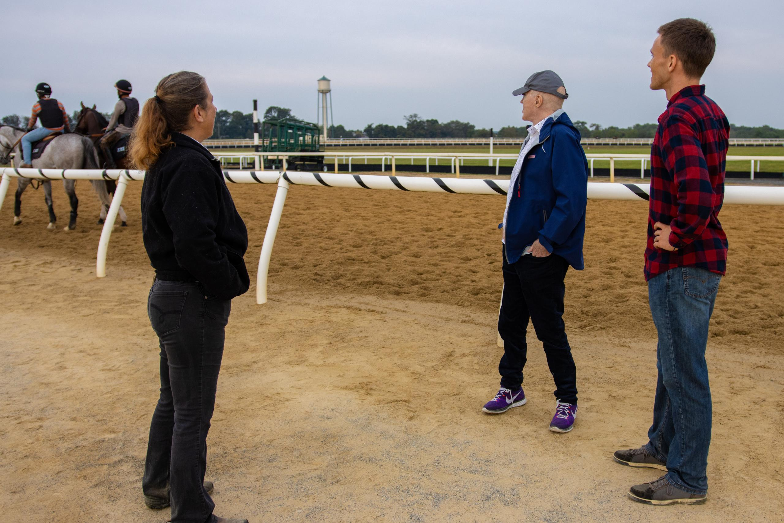 Racing partners watch their horse work out at the Fair Hill training facility track.