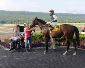 Euro Power, who is now available for breeding, stands in the winner's circle after her final race..