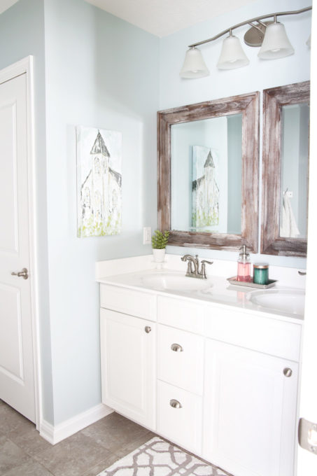 I'm sharing all of my favorite master bathroom organization ideas and some easy updates that we've done to take our master bathroom from cluttered and boring to organized and beautiful! | bathroom organization, organized bathroom vanity, how to organize a bathroom, how to organize deep vanity drawers, organized hair supplies, shaving tools organization, change out builder grade mirrors for wooden framed mirrors, church artwork