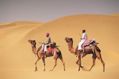 Two men on camelback in desert, Jaiselmer, India 546003