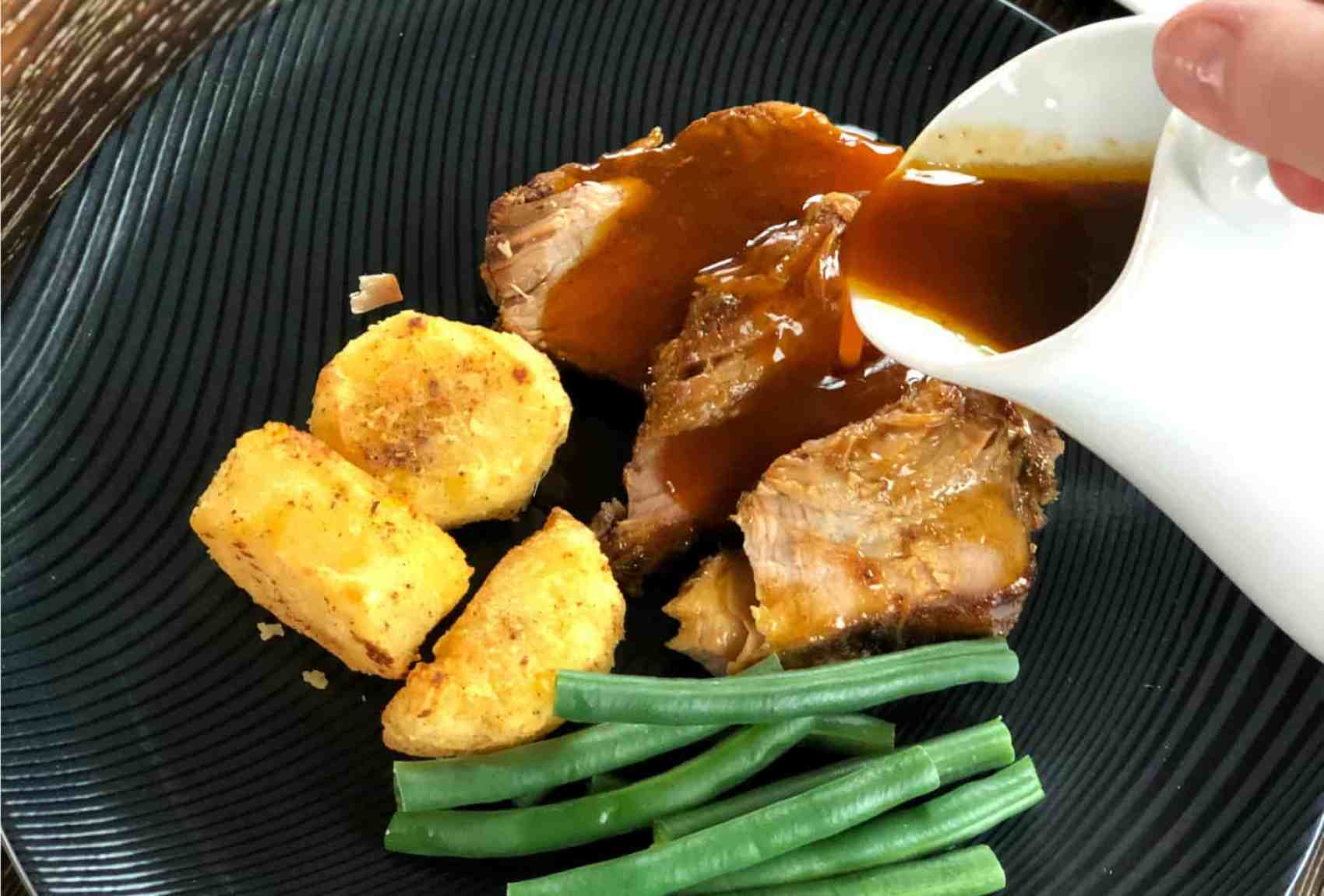 Pouring liberal amounts of gravy over pork